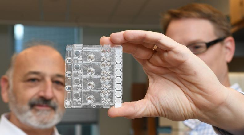 two men looking at microfluidic device